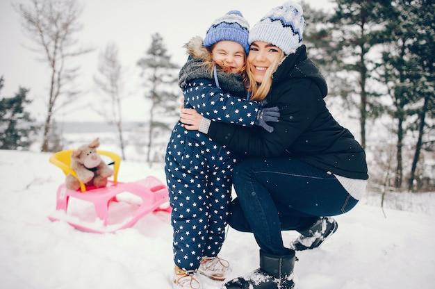 Petite fille avec sa mère jouant dans un parc d'hiver