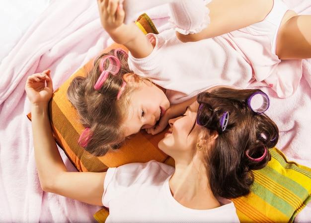 Petite fille avec sa mère jouant dans son lit