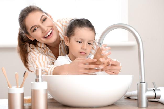 Petite fille avec sa mère se laver les mains dans la salle de bain