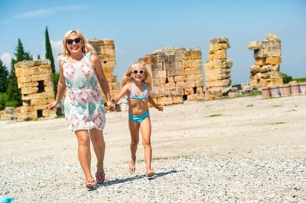 Une petite fille et sa mère se promènent dans les vieilles ruines de la ville de pamukkale. dinde