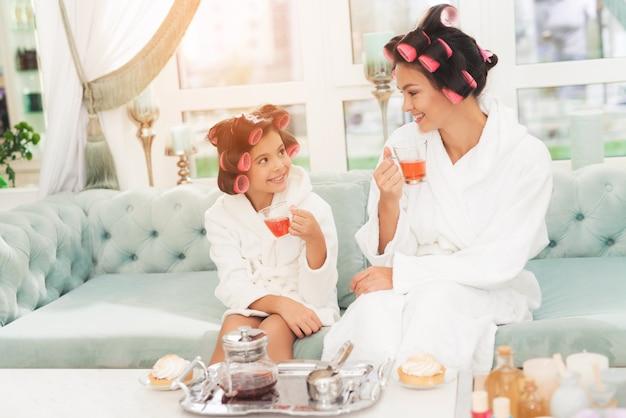 Une petite fille et sa mère sont assises sur un canapé