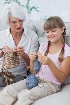 Petite fille et sa petite-fille tricoter ensemble