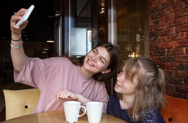 Une petite fille et sa sœur aînée prennent un selfie dans un café