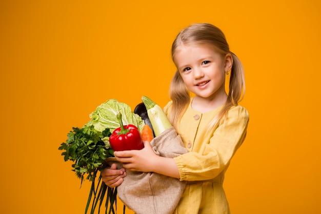 Petite fille avec un sac écologique et des légumes