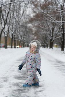 Petite fille en salopette marche dans un parc enneigé.