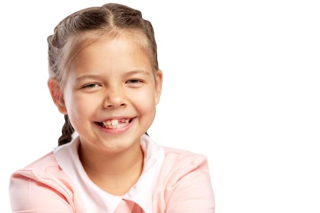 Une petite fille sans dent de devant rit. isolé sur fond blanc.