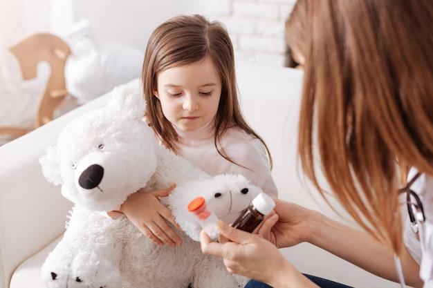 Petite fille sans joie tenant son jouet moelleux et va prendre des pilules pendant qu'un médecin professionnel lui donne des conseils