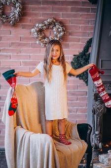 Petite fille de sapin de noël avec des chaussettes de noël
