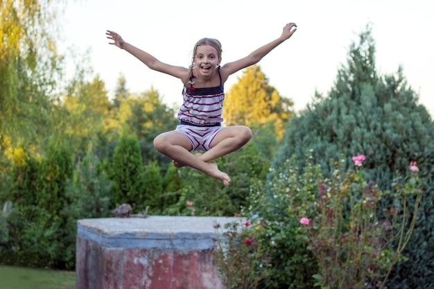 Petite fille sautant sur un trampoline dans le jardin