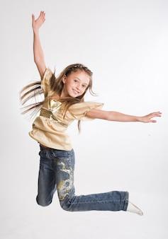 Petite fille saute sur fond blanc
