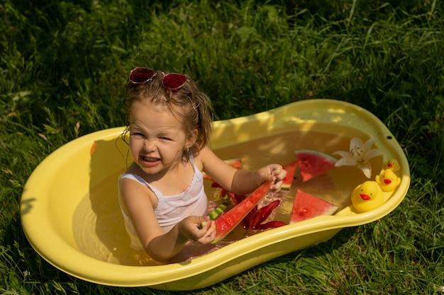 Une petite fille se baigne dans un bain jaune avec des fleurs et des canards dans la nature et mange une eau juteuse