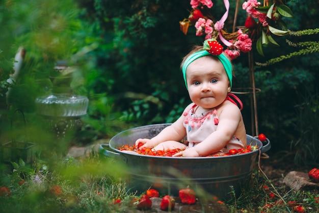Une petite fille se baigne dans un bassin avec des fraises dans le jardin.