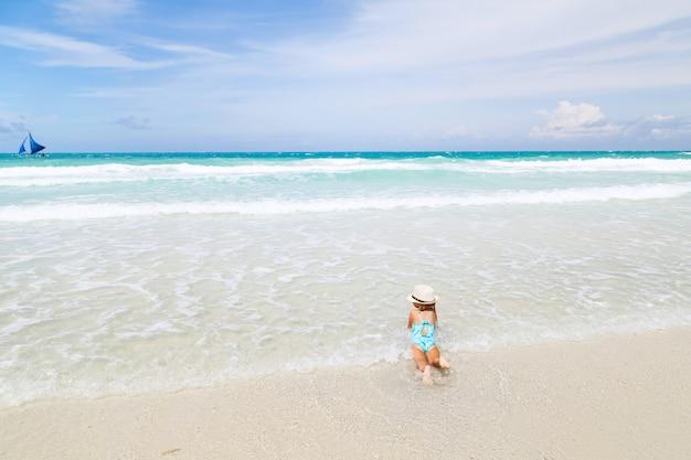 Petite fille se baigne dans la mer sur la plage de sable blanc