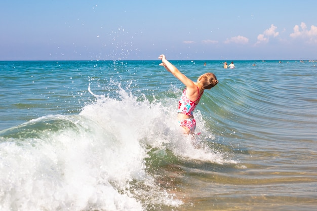 Une petite fille se baigne dans les vagues de la mer. du plaisir et du plaisir pendant les vacances d'été.