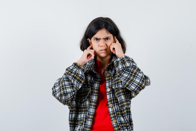 Petite fille se branchant les oreilles avec les doigts en chemise, veste et semblant en colère. vue de face.