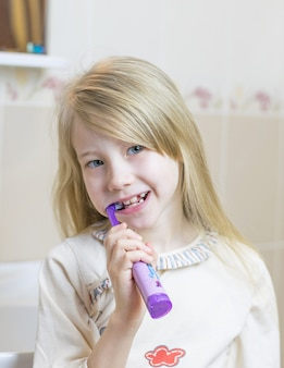 Une petite fille se brosse les dents avec une brosse à dents électrique.
