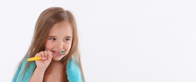 Une petite fille se brosse les dents