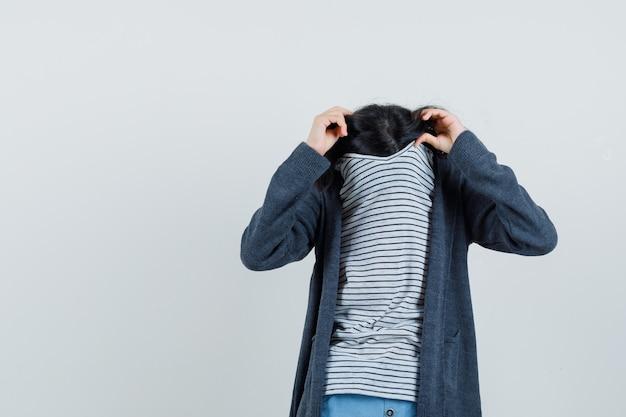 Petite fille se cachant le visage derrière le col en t-shirt, veste et à la gêne,