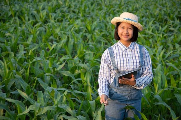 Petite fille se détendre et voir le suivi des produits dans le champ de maïs. les produits à base de maïs sont utilisés pour produire des aliments pour les humains et les animaux. concept d'agriculture.