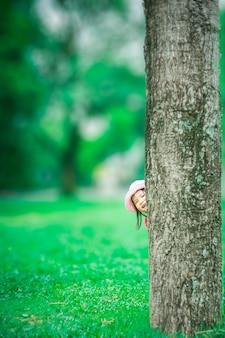 Petite fille se faufiler derrière l'arbre dans la forêt