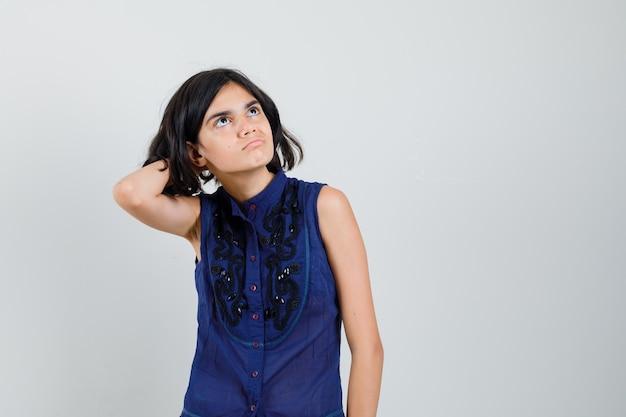 Petite fille se gratter la tête en chemisier bleu et à hésiter