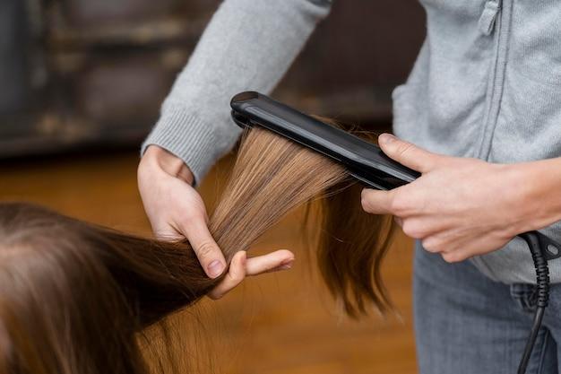 Petite fille se lissant les cheveux