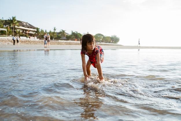 Petite fille se pencha et jouant du sable sur la plage