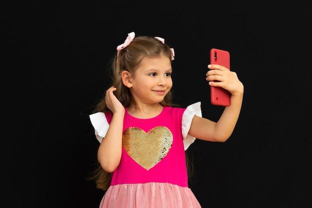 Une petite fille se prend en photo sur son téléphone.