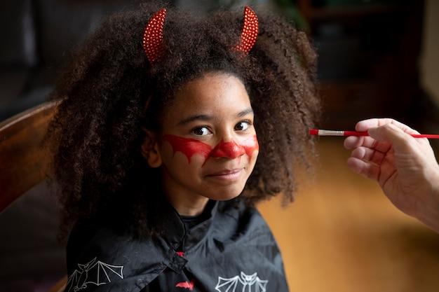 Petite fille se préparant pour halloween avec un costume de diable