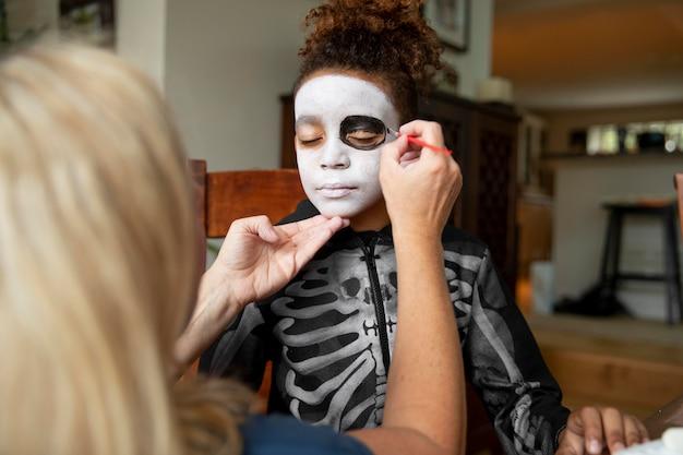 Petite fille se préparant pour halloween avec un costume de squelette