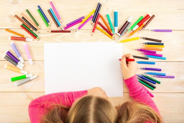 Petite fille se prépare à peindre sur une feuille de papier vierge.