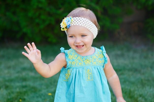 Petite fille se promène dans le parc sur l'herbe