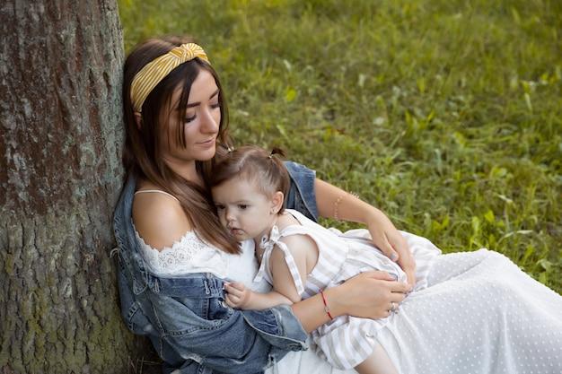 Une petite fille se promène avec sa mère à l'extérieur.