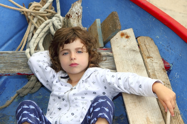 Petite fille se reposant sur un bateau baléare traditionnel