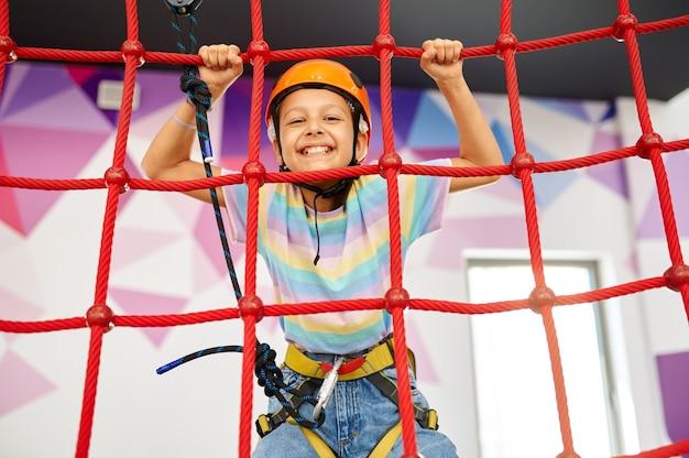 Petite fille se tenant aux cordes, tyrolienne