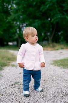 La petite fille se tient sur un chemin de gravier dans un parc verdoyant