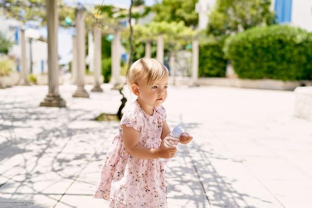 La petite fille se tient dans le patio et ouvre une bouteille d'eau