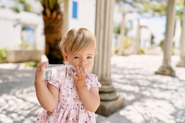 La petite fille se tient près d'une colonne et ronge une bouteille d'eau