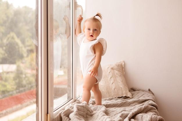Petite fille se tient sur le rebord de la fenêtre et regarde par la fenêtre
