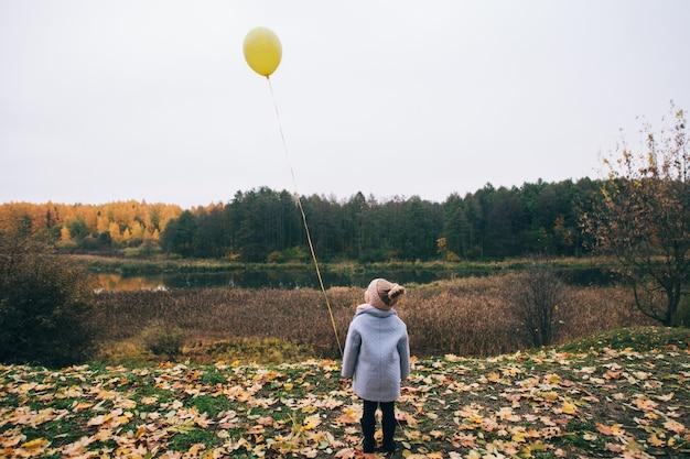 Une petite fille se tient avec son dos au parc d'automne et tient un ballon dans sa main