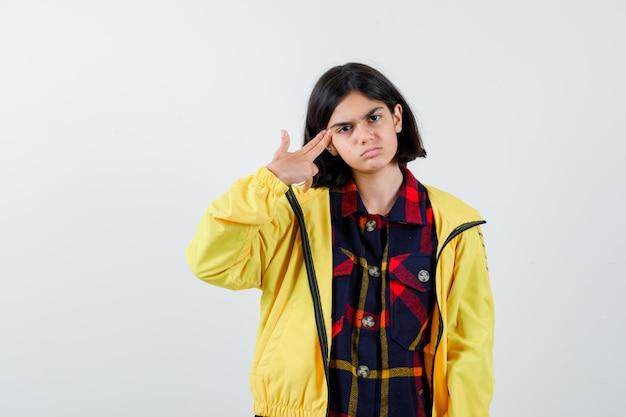 Petite fille se tirant avec une arme de poing en chemise à carreaux, veste et semblant désespérée, vue de face.