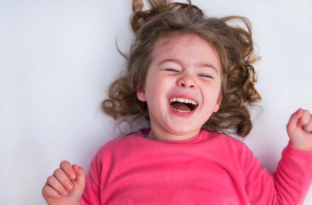 Petite fille se trouve sur le sol blanc et sourit.