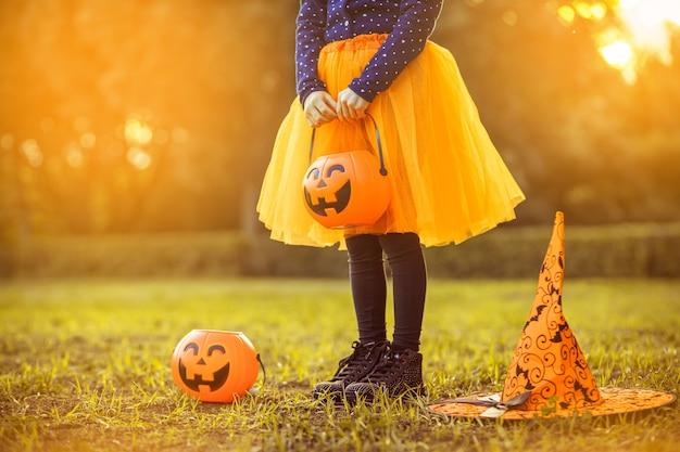 Petite fille avec seau de bonbons citrouille à l'extérieur