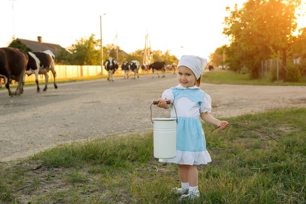 Une petite fille avec un seau à la main rencontre un troupeau de vaches revenant d'un pâturage dans le village