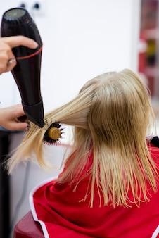 Petite fille sèche les cheveux dans le salon de coiffure.