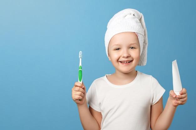 Une petite fille avec une serviette sur la tête tient une brosse à dents et un dentifrice.
