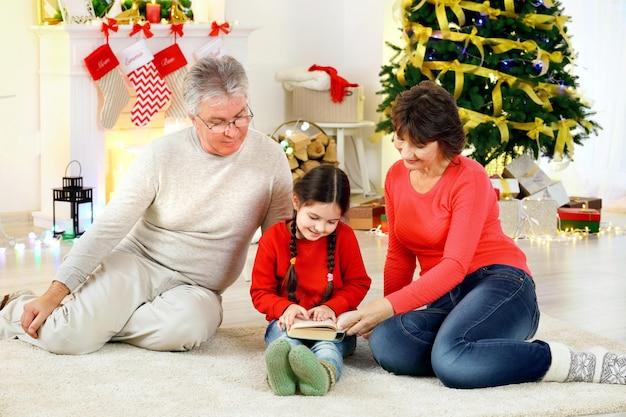 Petite fille et ses grands-parents lisant un livre dans le salon décoré pour noël