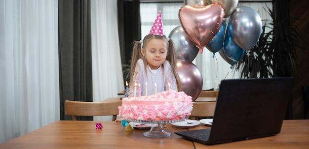 Petite fille seule fête son anniversaire avec un ordinateur portable d'appel vidéo en ligne. l'enfant dans la chambre.