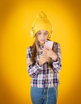 Petite fille avec smartphone et casque jaune mur