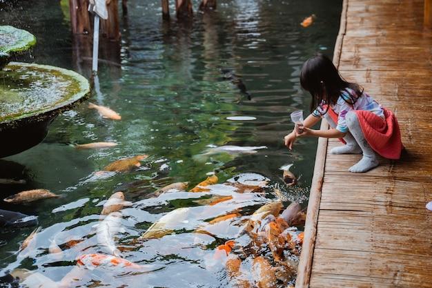 Petite fille et son amie nourrissent le poisson
